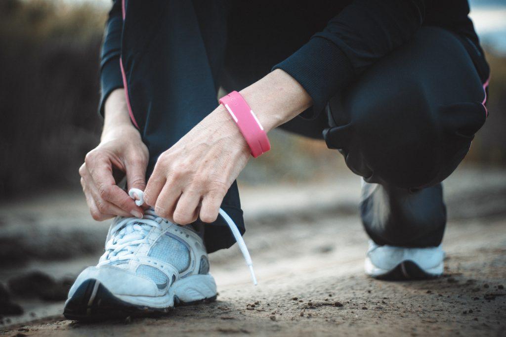 female jogger tying shoe laces